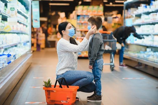 Madre e figlio indossano maschere protettive in un supermercato durante l'epidemia di coronavirus