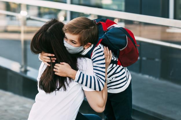 Madre e figlio che indossano maschere protettive all'aperto