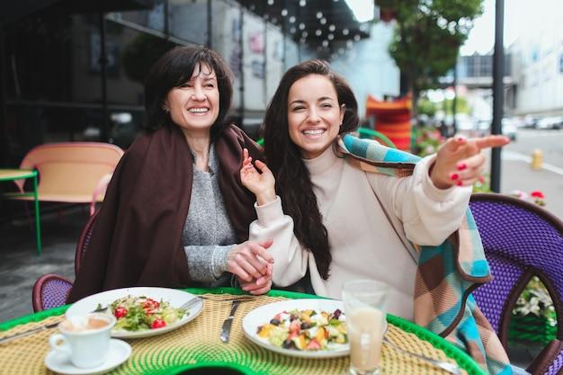 La madre e la sua giovane figlia si siedono insieme nella caffetteria