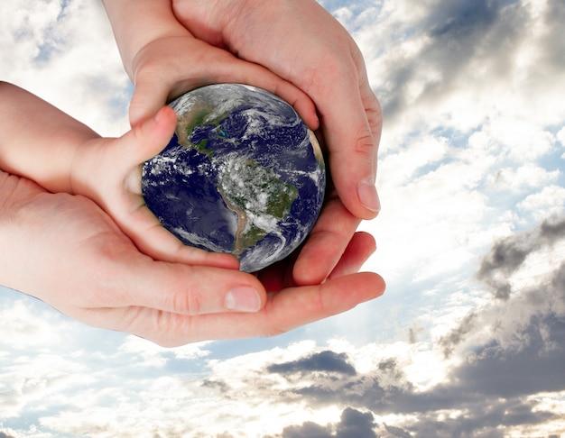 La madre tiene le mani del bambino con la terra sullo sfondo del cielo. elementi di questa immagine fornita dalla nasa