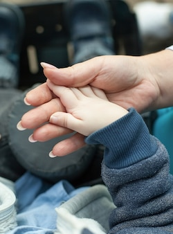 La madre tiene la mano del suo bambino disabile.