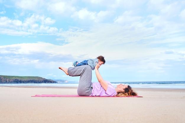 La madre tiene il suo bambino in grembo mentre pratica lo yoga su una spiaggia