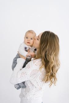 La madre tiene il figlio di cinque mesi tra le braccia contro un muro chiaro e lo bacia sulla guancia