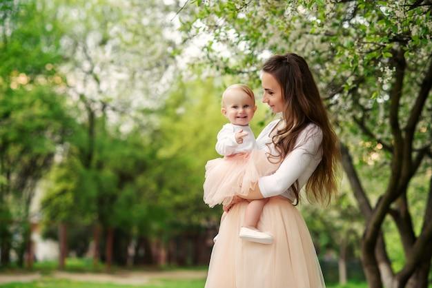 La madre tiene la sua piccola figlia tra le braccia tra alberi in fiore. mamma e il suo bambino indossavano un abito rosa dall'aspetto familiare.