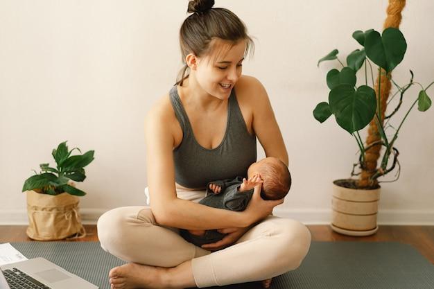 La madre tiene in braccio il figlio appena nato e lavora al computer a casa