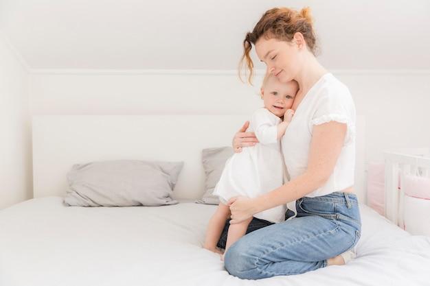 Madre che abbraccia la neonata sveglia a casa
