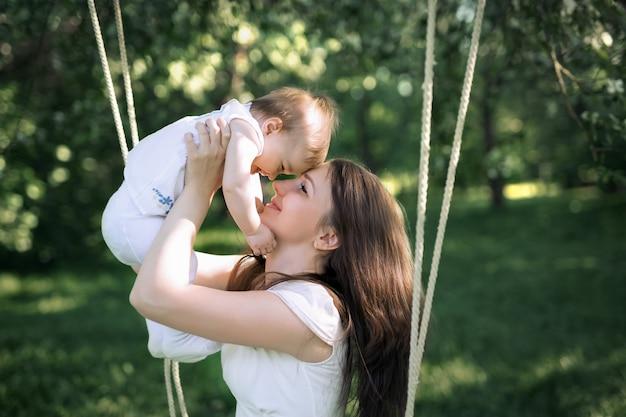 La madre tiene la sua piccola figlia tra le braccia, appoggiando delicatamente la fronte contro la fronte del bambino