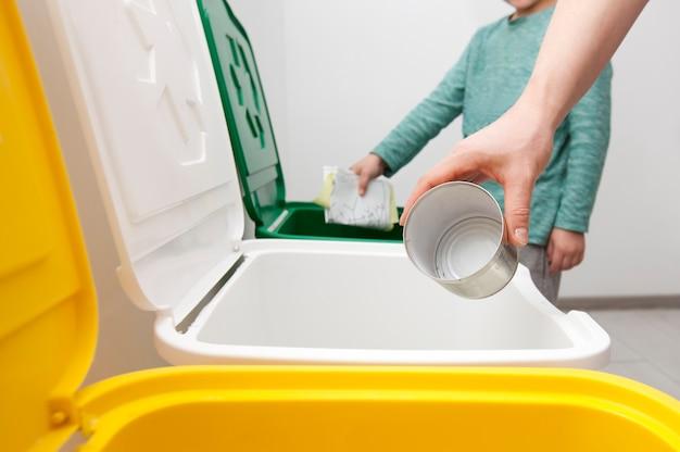 La madre sta insegnando a suo figlio come separare la spazzatura