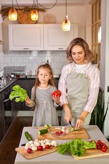 Madre e bambino ragazza che prepara cibo sano per la famiglia, insalata vegana a base di verdure fresche, intaglio insieme