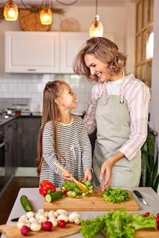 Madre e bambino ragazza che prepara cibo sano per la famiglia, insalata vegana a base di verdure fresche, mescolare insieme