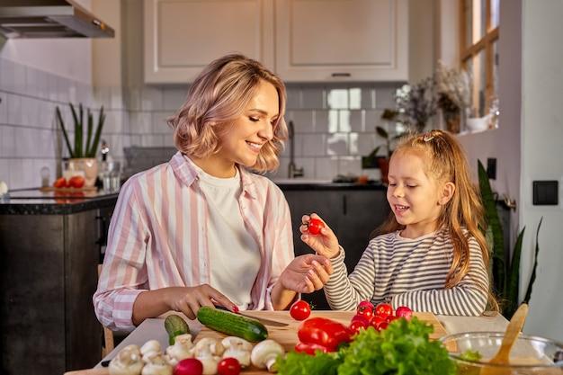 Ragazza del bambino e della madre che prepara cibo sano per la famiglia