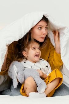 Madre e bambino che si nascondono sotto la coperta per divertimento