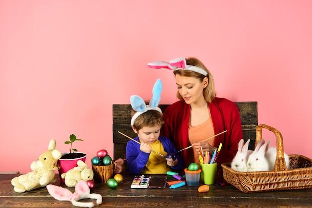 Madre e bambino che dipingono uova di pasqua giocattoli a sorpresa con uova