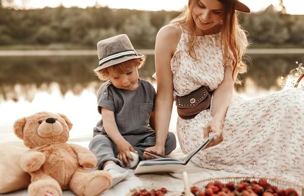 Madre e bambino che leggono un libro vicino al fiume