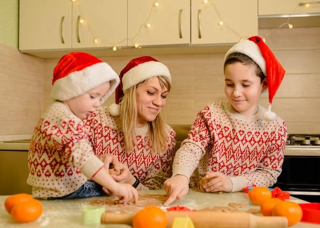 Madre e bambini che fanno i biscotti di pan di zenzero per natale