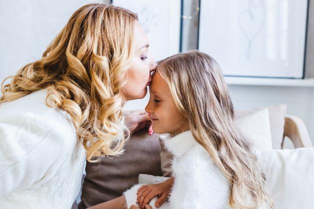 La madre bacia la figlia sulla fronte