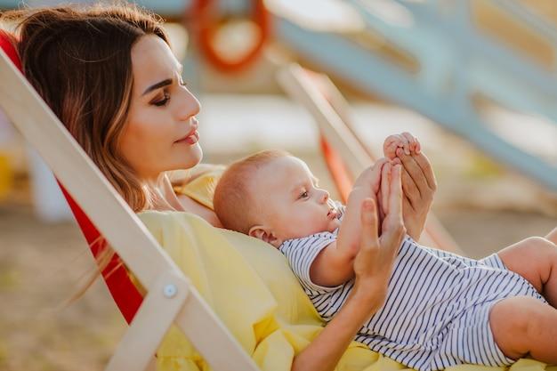 Madre sdraiata su una sedia a sdraio rossa che tiene in braccio il suo neonato