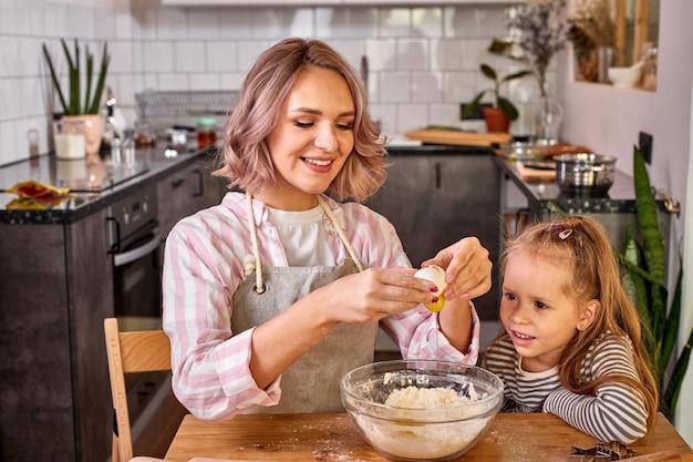 Madre e piccola figlia adorabile che cucinano insieme in cucina, bella mamma insegna ragazza carina del bambino che impasta la pasta per torta domestica preparando la sorpresa per la famiglia