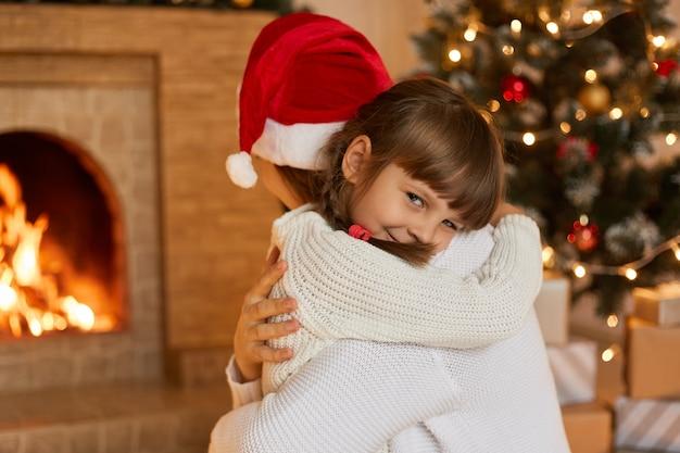 Madre e bambino che giocano a natale, signore che indossano maglioni bianchi, affascinante bambino guarda la telecamera con un sorriso