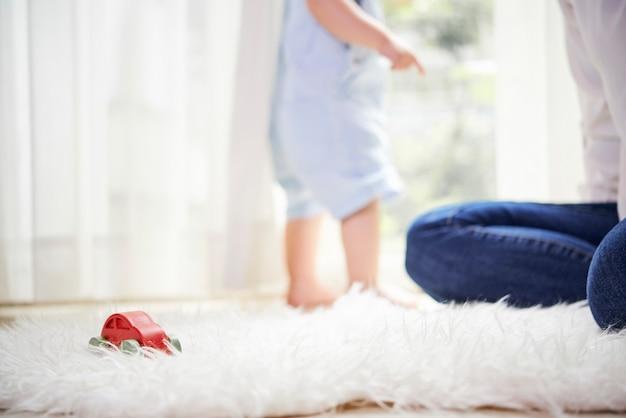 Madre e bambino che giocano sul tappeto di pelliccia a casa, messa a fuoco selettiva