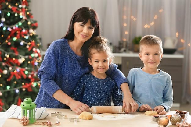 Madre e bambini piccoli che preparano i biscotti di natale in cucina