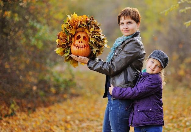 Madre e figlia sullo sfondo della foresta autunnale sorridenti abbracciando e tenendo in mano una lanterna di zucca-jack - un simbolo della festa di halloween.