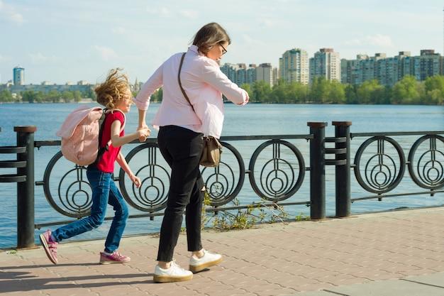 Madre e figlia piccola vanno a scuola la donna guarda l'orologio