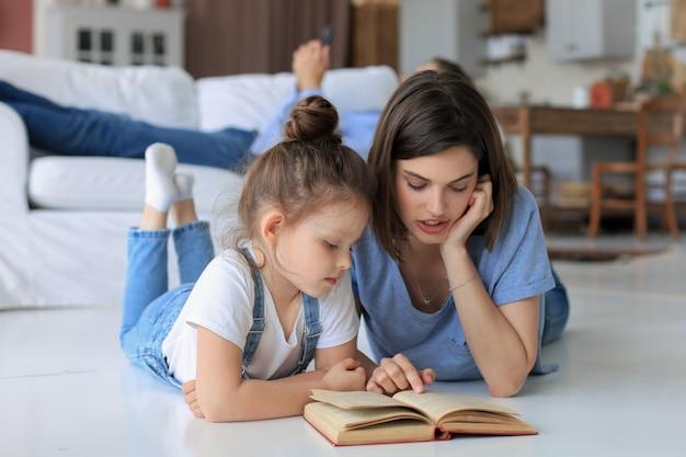 Madre e figlia hanno letto un libro insieme, sdraiate sul pavimento in soggiorno.