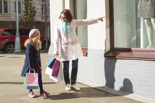 Madre e figlia piccola con borse della spesa