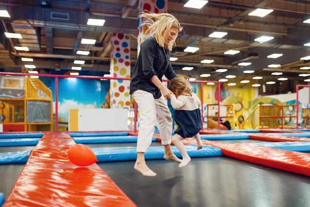 Madre e bambina che saltano su un trampolino nel centro di intrattenimento. la mamma e la figlia trascorrono le vacanze, la felicità dell'infanzia, i bambini felici nel parco giochi