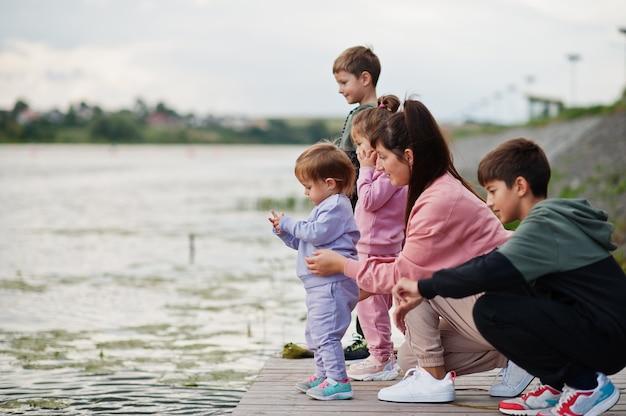 Amore materno. mamma con quattro bambini all'aperto sul molo. la grande famiglia sportiva trascorre il tempo libero all'aria aperta.