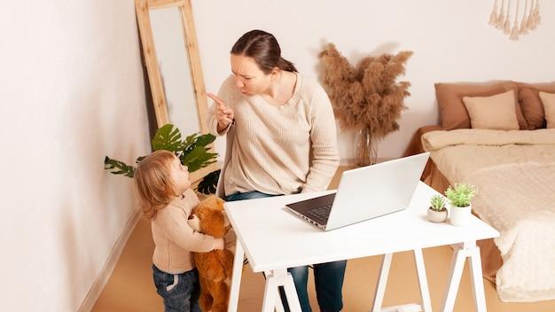 Una madre in congedo di maternità si siede davanti a un laptop e lavora un bambino che urla istericamente piange distrae