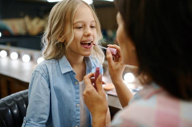 La madre dipinge le labbra di sua figlia nel salone di trucco
