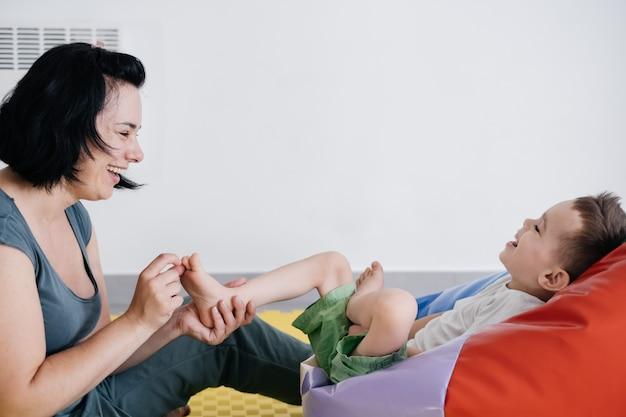 Madre che gioca con la paralisi cerebrale di un bambino disabile carino