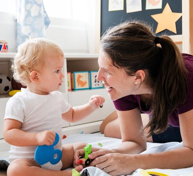 Madre che gioca con il suo bambino sul pavimento