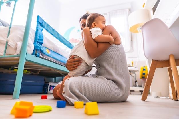 Madre che gioca con suo figlio e lo abbraccia amorevolmente