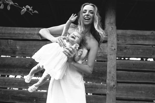 Madre che gioca con la sua piccola figlia nella fattoria