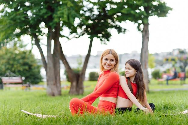 Madre a praticare yoga con sua figlia all'aria aperta