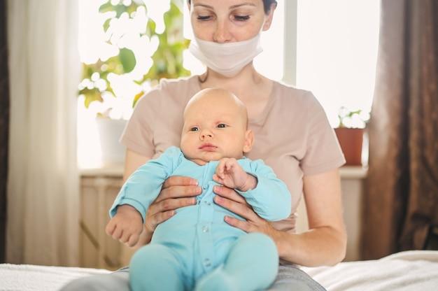 Madre in maschera protettiva che tiene il suo figlio neonato