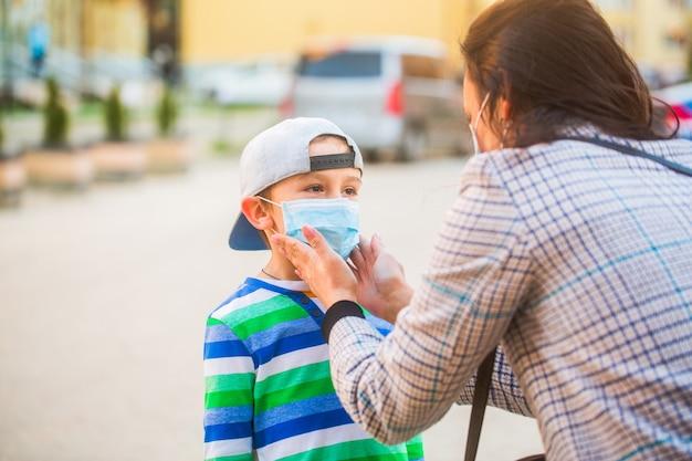 La madre mette a suo figlio una maschera protettiva per il viso all'aperto.
