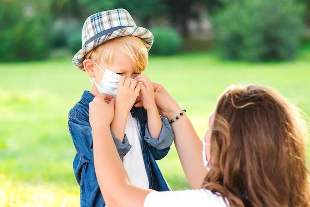 La madre indossa la mascherina medica per il piccolo figlio all'aperto. coronavirus e vita reale. maschera medica per prevenire il coronavirus. quarantena per il coronavirus.