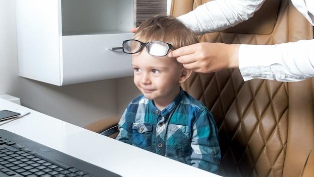 Madre che mette gli occhiali sul suo piccolo figlio seduto in sedia da ufficio.