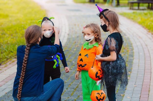 Madre che mette una maschera protettiva sul suo bambino durante la pandemia di covid19 ad halloween