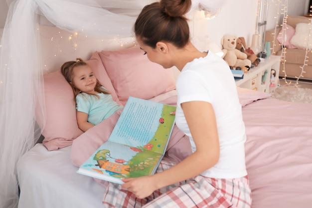 Madre che legge la favola della buonanotte alla sua piccola figlia a casa