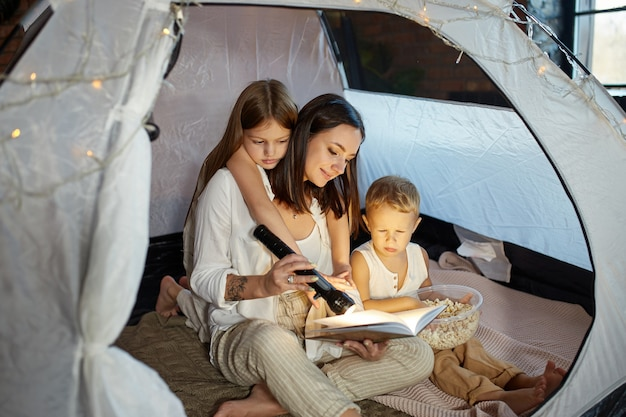 La madre legge un libro di fiabe per i suoi figli mentre è seduta in una tenda di notte. mamma figlio e figlia che leggono un libro con una torcia in mano