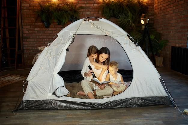 La madre legge un libro di fiabe per i suoi figli mentre è seduta in una tenda di notte