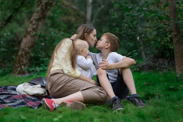 Madre che riposa con due bambini in natura. picnic in famiglia nel parco. la mamma bacia il figlio