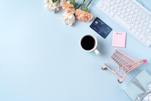 Concetto di design regalo acquisto festa della mamma con fiore di garofano su sfondo scrivania tavolo blu ufficio