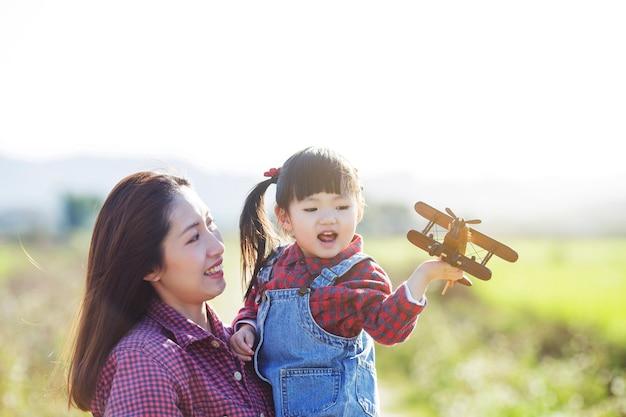 Concetto, madre e figlia di festa della mamma che giocano all'aperto, concetto di crescita