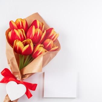 Concetto di design per la festa della mamma, mazzo di fiori di tulipano, - bellissimo bouquet rosso e giallo isolato su sfondo bianco brillante tavolo, vista dall'alto, piatto, spazio di copia